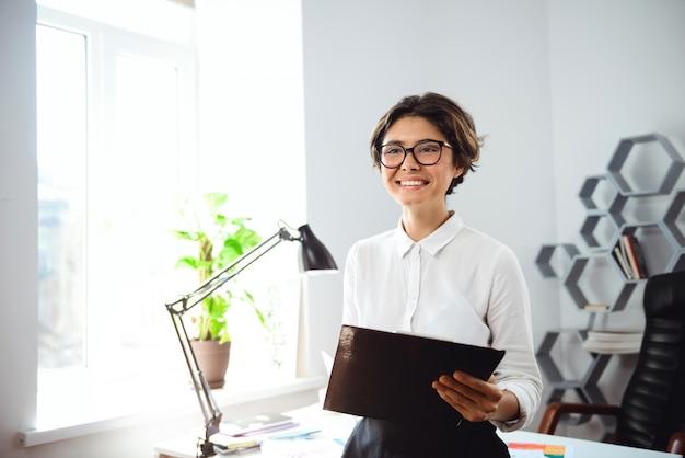 Młoda piękna bizneswomanu mienia falcówka, ono uśmiecha się przy miejscem pracy w biurze.