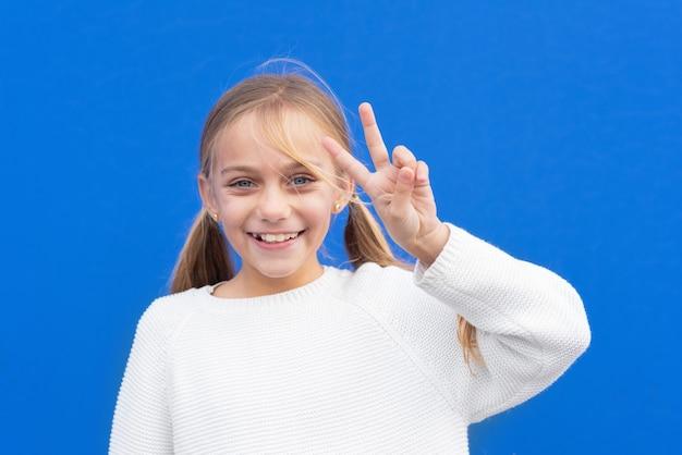 Młoda piękna blond dziewczyna pokazuje palce robi znak zwycięstwa. numer dwa.