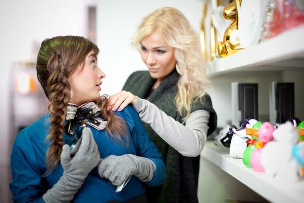 Młoda piękna blond kobieta dotykając kobieta sprzedawca w sklepie z pamiątkami przez ramię, aby zapytać