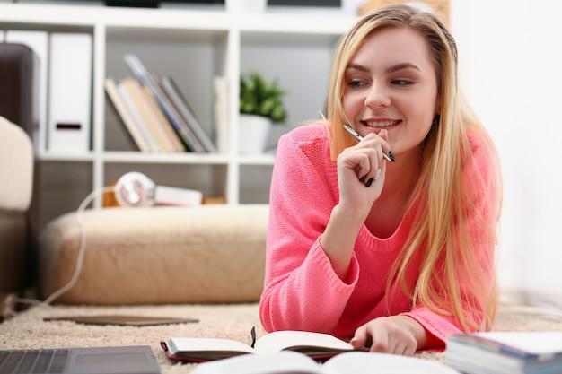 Młoda piękna blond kobieta leży na podłodze czytać książkę