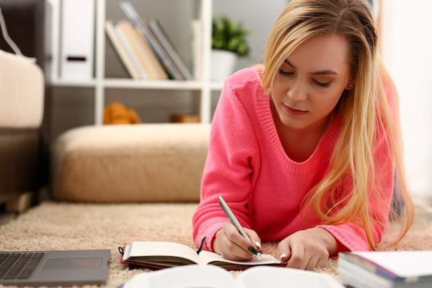 Młoda piękna blond kobieta leży na podłodze i czyta książkę