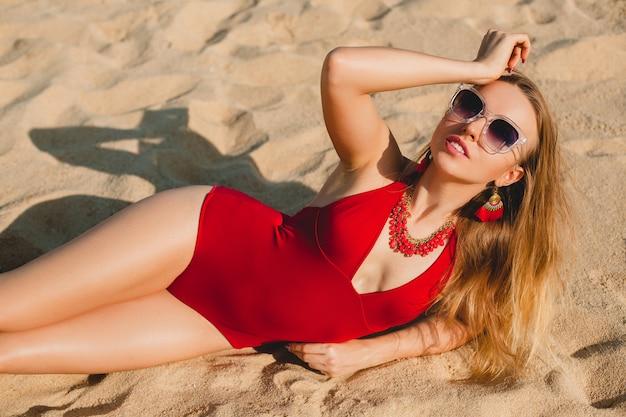 Młoda piękna blond kobieta opalając się na piaszczystej plaży w czerwonym kostiumie kąpielowym, okulary przeciwsłoneczne