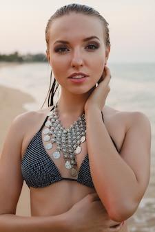 Młoda piękna blond kobieta opalając się na piaszczystej plaży w kostiumie kąpielowym bikini, naszyjnik vintage