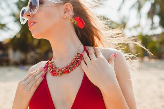 Młoda piękna blond kobieta opalając się na plaży w czerwonym kostiumie kąpielowym, okulary przeciwsłoneczne
