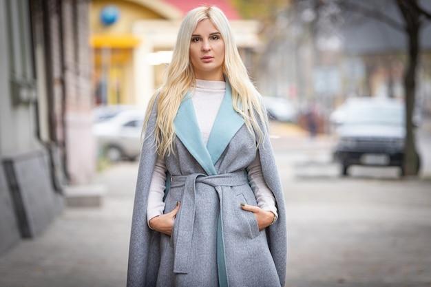 Młoda piękna blond kobieta w jesiennym płaszczu stoi na ulicy miasta. nieostrość. modna koncepcja.