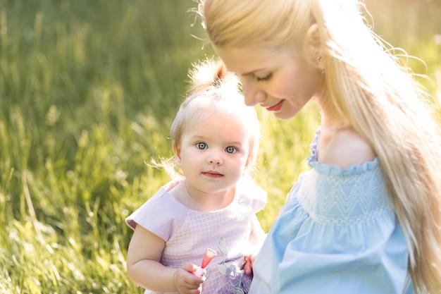 Młoda piękna blondynka matka z córeczką śmiejącą się razem i bawiąca się w zielonym parku