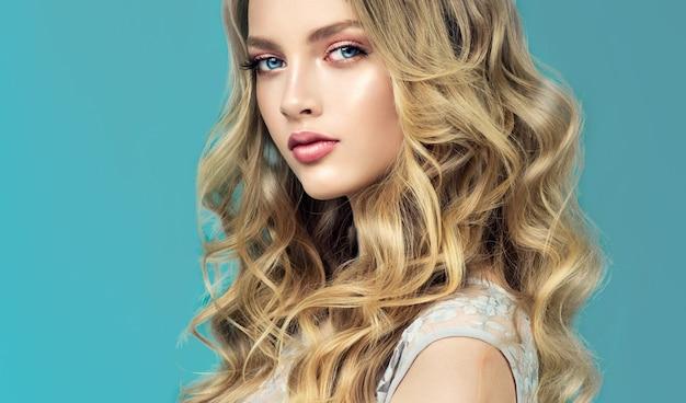 Młoda, piękna blondynka o długich, falistych, zadbanych i kędzierzawych włosach. stylowa, luźna fryzura z swobodnie układającymi się lokami. sztuka fryzjerska, pielęgnacja włosów i makijaż.