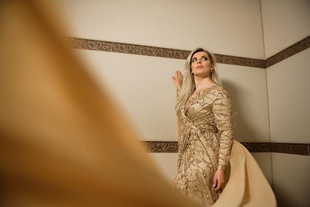 Młoda piękna blondynka plus rozmiar model w sukni, kobieta portrecie, makeup i fryzurze