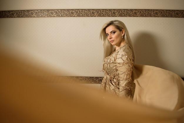 Młoda piękna blondynka plus rozmiaru model w sukni, kobieta portrecie na beżu, makeup i fryzurze