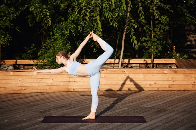 Młoda piękna blondynka praktykuje jogę na zewnątrz o wschodzie słońca