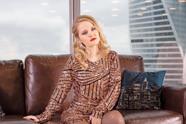 Młoda piękna blondynka siedzi na skórzanej kanapie na tle panoramicznego okna z widokiem na wieżowce i duże miasto.