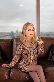 Młoda piękna blondynka siedzi na skórzanej sofie z lampką szampana na powierzchni panoramicznego okna z widokiem na drapacze chmur i duże miasto