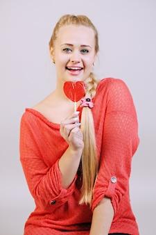 Młoda piękna blondynka trzyma lizaka