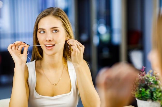 Młoda piękna blondynka używa nici dentystycznej do pielęgnacji zębów.