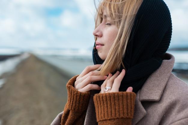 Młoda piękna blondynka w czarnym szaliku stoi na środku autostrady z zamkniętymi oczami na tle błękitnego nieba.