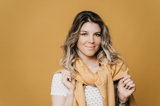 Młoda piękna blondynka w jasnej koszulce i żółtym swetrze zawiązanym na szyi, słodko uśmiechnięta i delikatna, na żółtym tle. ludzie szczere emocje, koncepcja stylu życia.