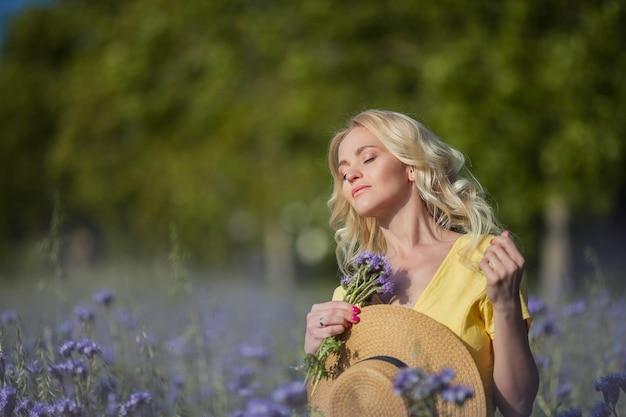 Młoda piękna blondynka w kapeluszu idzie przez pole fioletowych kwiatów. lato. wiosna.