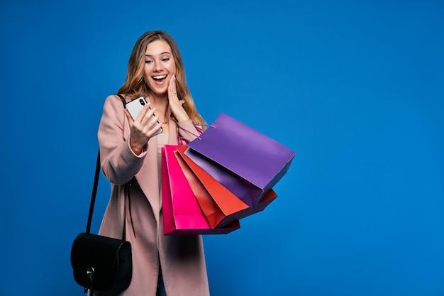 Młoda piękna blondynka w kurtce na niebieskiej ścianie z telefonem komórkowym robi zakupy online.