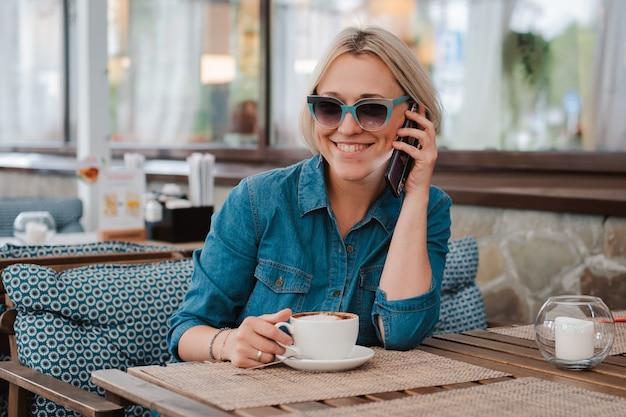Młoda piękna blondynka w letni poranek w okularach przeciwsłonecznych komunikuje się na telefonie komórkowym w kawiarni przy filiżance kawy cappuccino. .