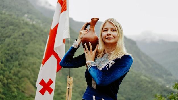 Młoda piękna blondynka w narodowych gruzińskich strojach na tle gruzińskiej flagi i gór