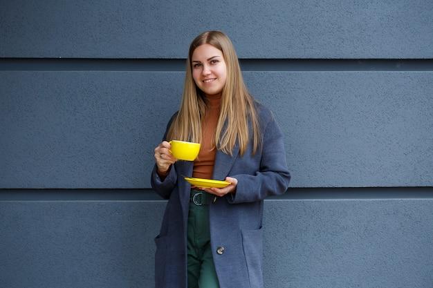 Młoda piękna blondynka w szarym płaszczu pije gorącą herbatę z żółtej filiżanki w zimny jesienny dzień. pyszny ciepły napój na tarasie w kawiarni