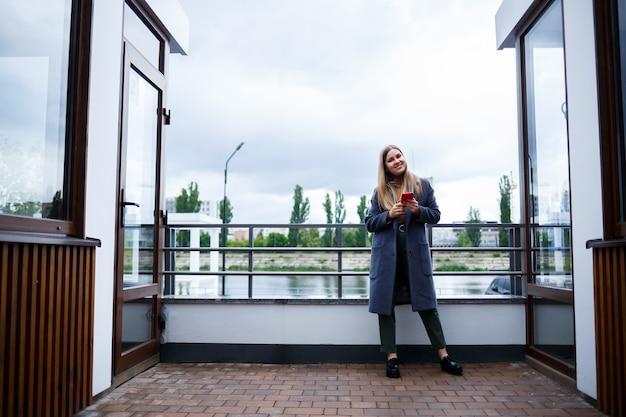 Młoda piękna blondynka w szarym płaszczu rozmawia przez telefon w zimny jesienny dzień. dziewczyna z telefonem na tarasie z widokiem na rzekę