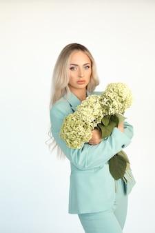Młoda piękna blondynka z długimi włosami w miętowym zielonym spodniach z naręczem kwiatów hortensji w ramionach. portret.