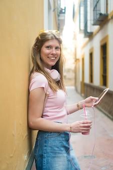 Młoda piękna blondynka ze słuchawkami i ogromnym uśmiechem na twarzy patrząc na kamerę