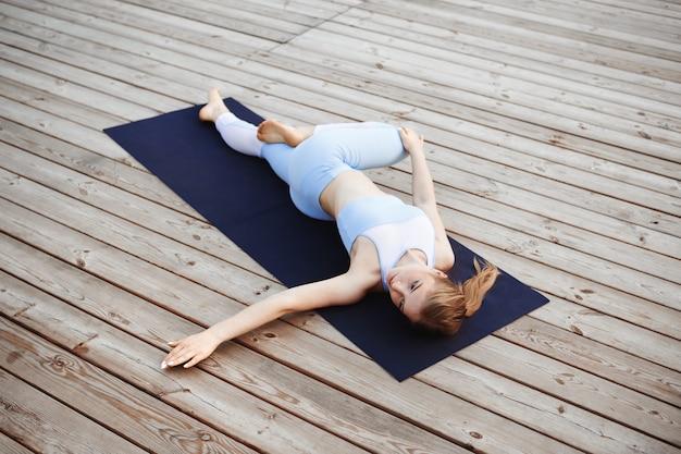 Młoda piękna blondynki dziewczyna ćwiczy joga outside.