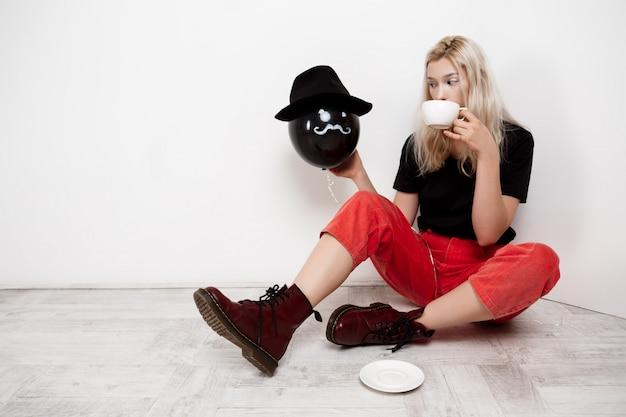 Młoda piękna blondynki dziewczyna trzyma czarnego baloon w kapeluszowym obsiadaniu na podłoga pije kawę nad biel ścianą.