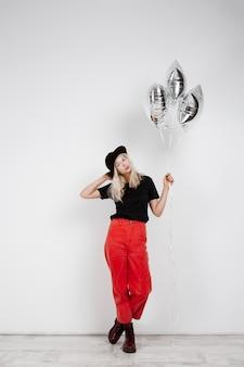 Młoda piękna blondynki dziewczyna trzyma srebnych baloons nad biel ścianą.