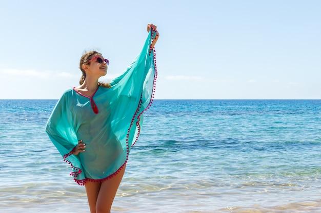 Młoda piękna blondynki dziewczyna w szkłach ma zabawę na plaży