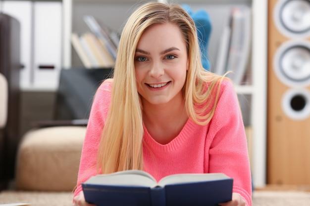 Młoda piękna blondynki kobieta kłama na podłogowej czytelniczej książce