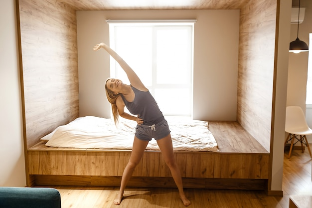Młoda piękna blondynki kobieta robi do domu ćwiczy w ranku. stoi w pokoju i pochyla się na bok. ciało rozciągające. sam. światło dzienne.