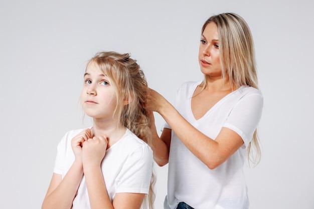 Młoda piękna blondynki kobieta robi fryzurze dla dziewczyny. wspólny wypoczynek matki i córki. pojedynczo na białym tle