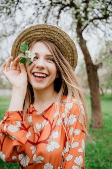 Młoda piękna blondynki kobieta w kwitnącym ogródzie. kwitnące wiosną drzewa. pomarańczowa sukienka i słomkowy kapelusz.