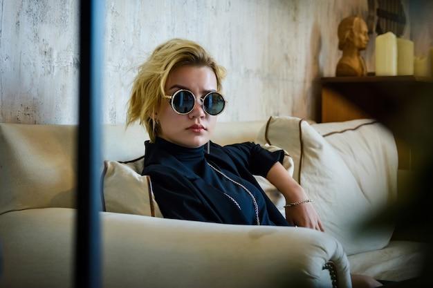 Młoda piękna blondynki kobieta z okularami przeciwsłonecznymi, siedzi w kanapie, wnętrze dom