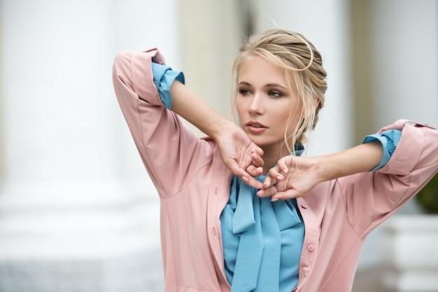 Młoda piękna blondynki kobieta z splecionym włosy plenerowym. kobieta w niebieskiej sukience chodzi po ulicach miasta.