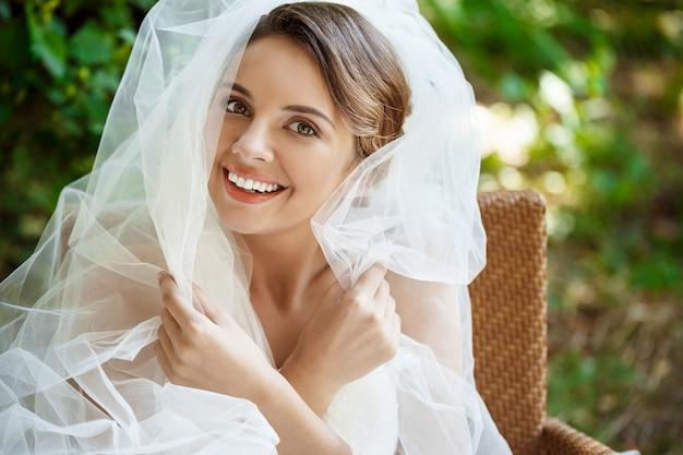Młoda piękna blondynki panna młoda w ślubnej sukni i przesłony ono uśmiecha się.