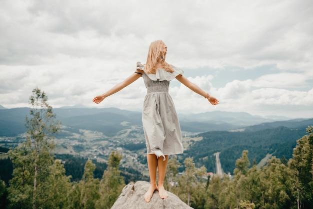 Młoda piękna bosa blondynka z długimi włosami w letniej sukience stoi na szczycie góry