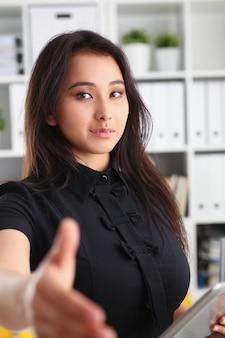 Młoda piękna brunetka bizneswoman pożyczyć rękę do przodu