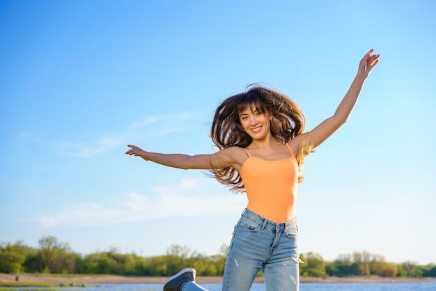 Młoda piękna brunetka dziewczyna w dżinsach i pomarańczowej koszulce skacze na tle nieba w słoneczny letni dzień