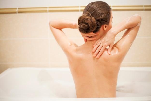 Młoda piękna brunetka kobieta bierze kąpiel w domu