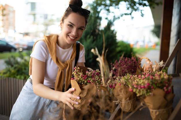 Młoda piękna brunetka kobieta ciesząca się kwiatami w doniczkach na werandzie kwiaciarni
