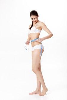 Młoda piękna brunetka kobieta mierzy jej idealną talię z niebieską miarką