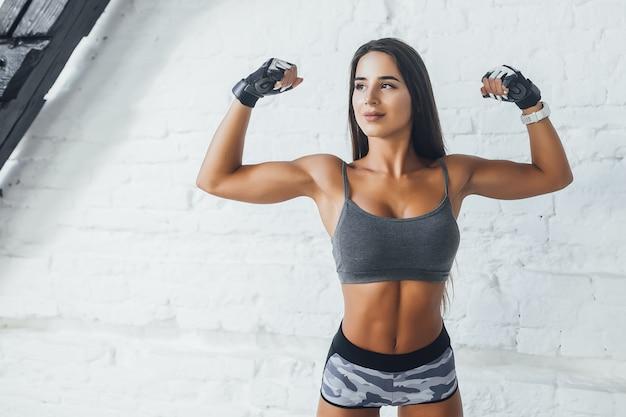 Młoda piękna brunetka kobieta pokaż musculs na poddaszu siłowni