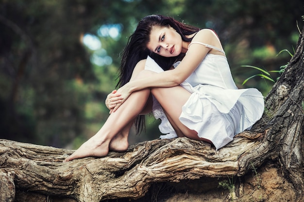 Młoda piękna brunetka kobieta siedzi i odpoczywa w lesie