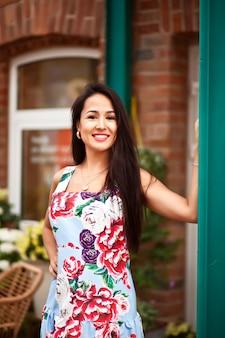 Młoda piękna brunetka kobieta z kwiatami we włosach i kolorowe sukienki. hiszpanka