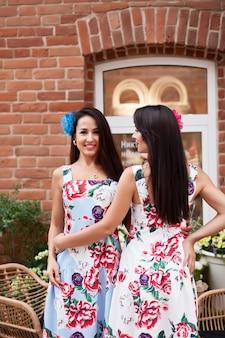 Młoda piękna brunetka kobiety z kwiatami we włosach i kolorowe sukienki. hiszpanka