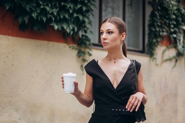Młoda piękna brunetka pije kawę i spaceruje po mieście